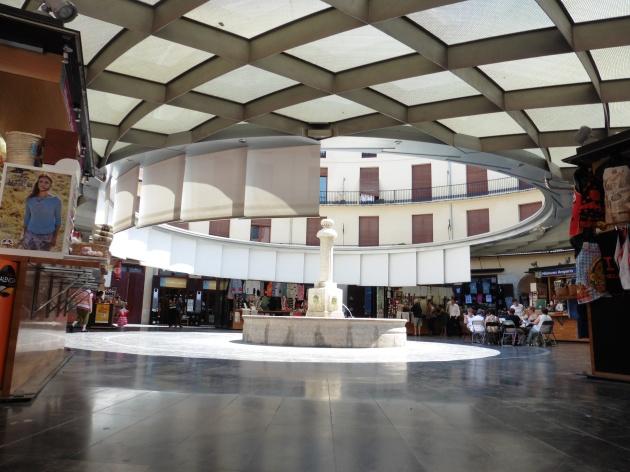 Vistas de las Tiendas de la Plaza Redonda y mujeres bordando al fondo